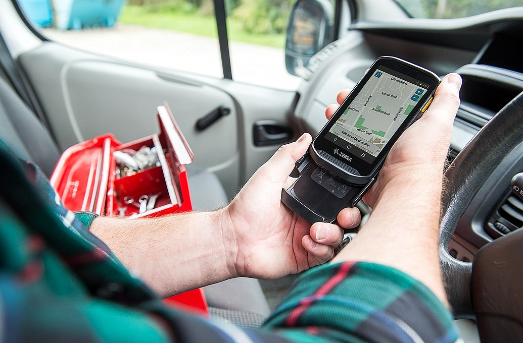 worker checking phone sitting in car