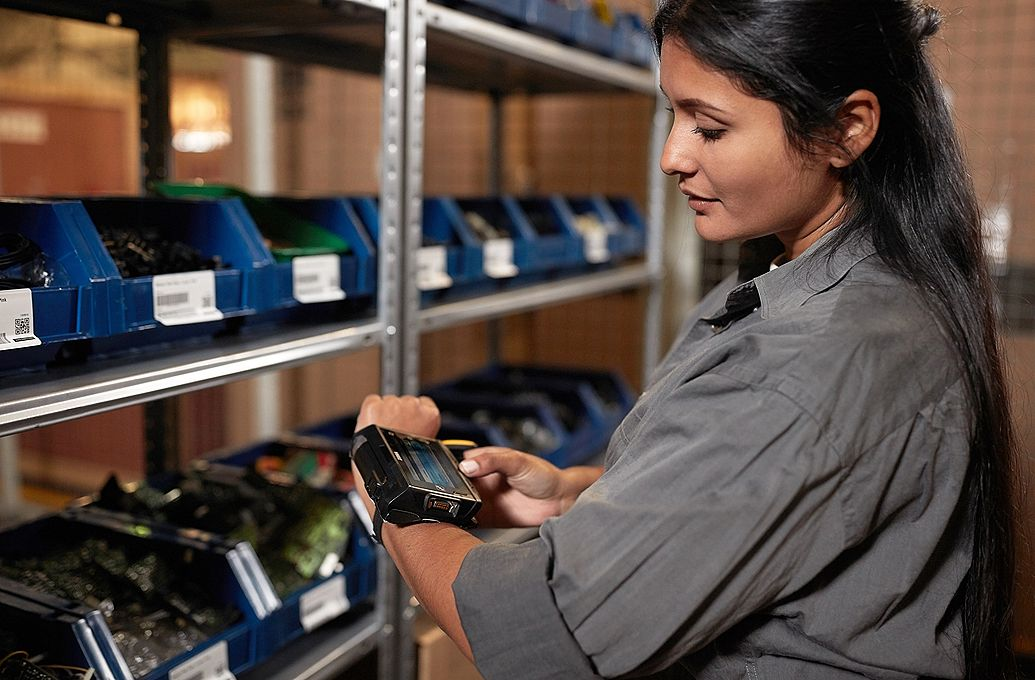 woman using wrist computer device in warehouse