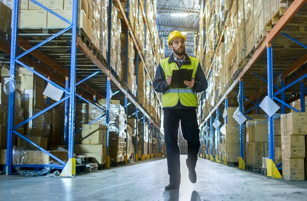 Man walking in warehouse with clip-board