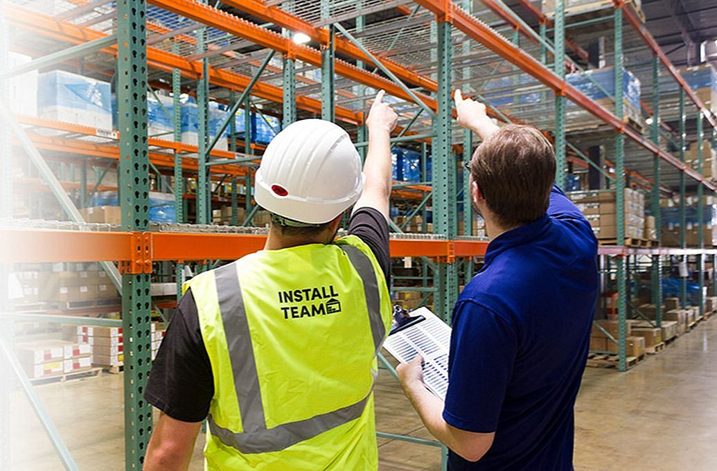 two men in warehouse pointing at shelve